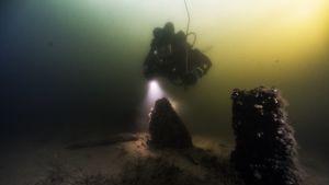 Vedenalainen kuva, jonka etualalla pari pilaria ja taustalla sukeltaja, jolla kädessään taskulamppu.