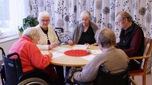 Vanhukset pelaavat bingoa hyvinvointiasemalla.