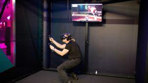 mies pelaa virtuaalipeliä