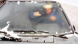 Mies pyyhkii auton huurtunutta tuulilasia.