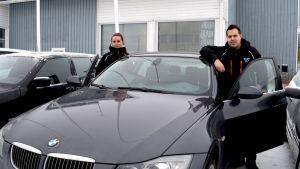 Autokauppiaat Laura ja Miika Pallari nojailevat myyntiartikkeliin liikkeensä pihalla Tervolassa.