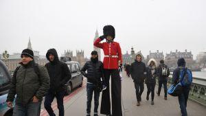 Turisteja viihdytetään Britannian parlamenttitalon edustalla.
