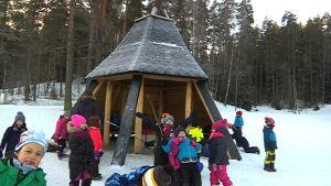 Lapsia talvella kodan edessä