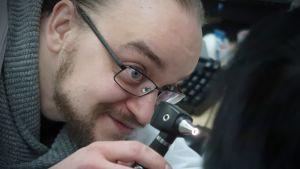 Lääkäri Joonas Joensuu tutkii potilaan nielua.