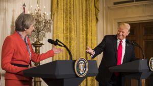 Punapukuinen nainen ja mustapukuinen mies seisovat puhujanpöntöissä ja ojentavat kättä toistensa suuntaan.