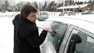 Janek Stefanoff raappaa auton ikkunoita.