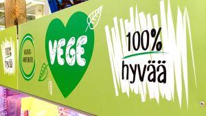 Vegaanisia tuotteita sisältävän elintarvikehyllyn tunnuslogo: vihreä sydän ja teksti 100% hyvää.