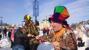 Värikkäisiin asuihin pukeutuneet ihmiset vetävät köyttä lumisella torilla.