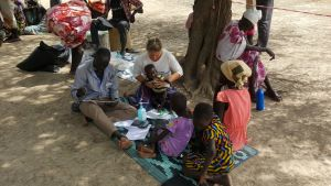 Pieni lapsi istuu maassa istuvan naislääkärin sylissä. Ympärillä istuu kaksi muuta aikuista ja kaksi lasta. Taustalla näkyy useita sivullisia.