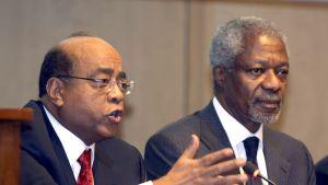 Mo Ibrahim puhuu mikrofoniin. Kofi Annan istuu vieressä.