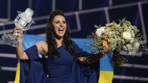 Kuvassa Ukrainan artisti Jamala Euroviisuvoittonsa jälkeen Tukholmassa viime toukokuussa. Laulajalla on oikeassa kädessään pokaali ja vasemmassa kädessään kukkakimppu.