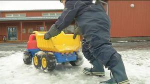 lapsi työntää leluautoa ulkona