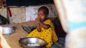 lapsi syö ruokaa pakolaisleirillä lähellä Mogadishua.