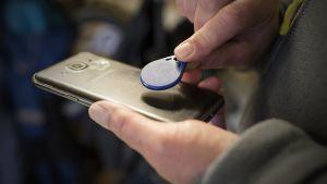 Käsi pitelee RFID-tagia älypuhelimen lähellä.