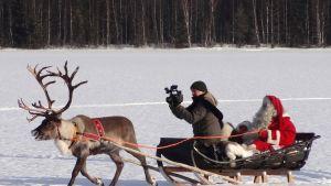 Poro vetää reessä istuvaa joulupukkia ja kuvaavaa kameramiestä lumisen järven jäällä Pellossa.