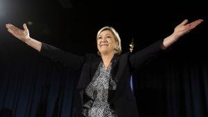 Kuvassa Marine Le Pen tuulettaa lavalla kampanjatilaisuudessa.