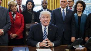 Donald Trump lähipiirinsä ympäröimänä Valkoisessa talossa maanantaina 13. maaliskuuta.