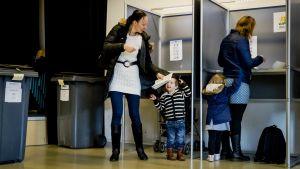 Nainen ja lapsi äänestyskopissa. Viereisestä kopista lähtee toinen nainen lapsensa kanssa.