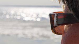 Henkilö katsoo järvelle aurinkolasit päässä.