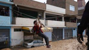 Perun poliisi pelastaa ihmisiä tulvan tieltä maan pääkaupunki Limassa 17.3.2017.
