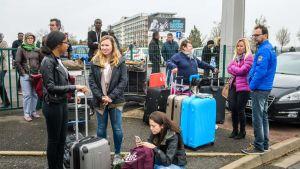 Evakuoidut matkustajat odottavat matkalaukkojensa kanssa metalliaidan luona Orlyn lentokentän eteläisen terminaalin uudelleenavautumista Pariisissa.