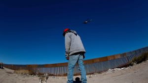Yhdysvaltain ja Meksikon välistä raja-aitaa. Mies leikkii koiransa kanssa, sinisellä taivaalla lentää helikopteri.