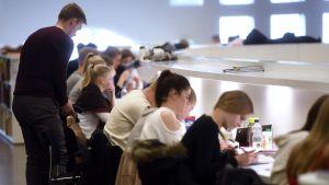 Nuoria ihmisiä opiskelemassa.