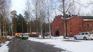 Hälytysajoneuvoja punatiilisen rakennuksen ulkopuolella.