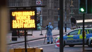 Rikospaikkatutkija kuvaamassa terrori-iskun paikalla Lontoossa keskiviikkona.