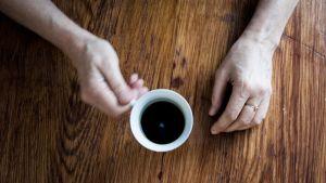 Henkilön kädet pöydällä, kädessä valkoinen kahvikuppi.