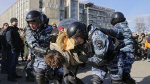 Kaksi OMON-mellakkapoliisia kuljettaa välissään mielenosoittajaa. Kolmas poliisi suojaa poliisien selustaa. Taustalla näkyy mielenosoittajia ja Izvestija-lehden rakennus.