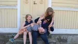 nainen ja kolme lasta istuvat portailla
