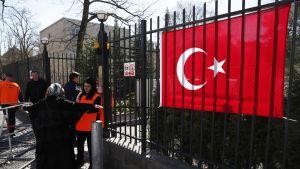 Portti, jonka vieressä roikkuu suuri Turkin lippu. Huivipäinen nainen kädet levällään turvatarkastuksessa.