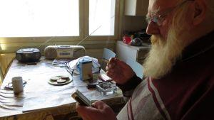 Veijo Sahlberg tupakoi ja selaa puhelintaan