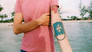Mies näyttää käsivarttaan, jossa on vaakuna-tatuointi.