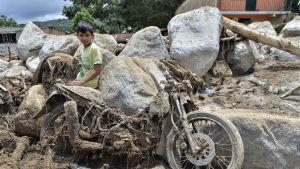 Nuori poika istuu kivellä, lähellä pahoin likaantunutta ja vaurioitunutta moottoripyörää.