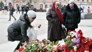 Ihmiset laskivat kukkia Sennajan metroasemalle Pietarissa 4. huhtikuuta.