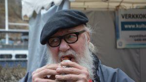mies syö makkaraa