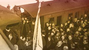 Asessori P. E. Svinhufvud on saapunut Siperian karkotusmatkaltaan Viipurin asemalle maaliskuun lopussa 1917. P. E. Svinhufvud veturin edessä kukat kädessä.