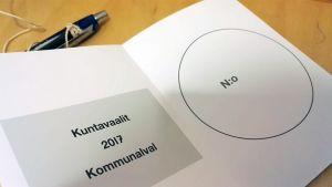Tyhjä kunnallisvaalien äänestyslippu ja kynä äänestyskopissa