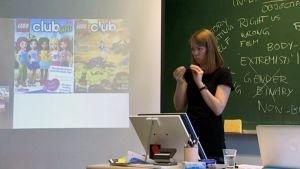 Feminismikurssin luennoitsija viittomassa luokkahuoneen etuosassa.