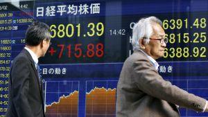 Jalankulkijoita Tokion kadualla, taustalla näkyvissä elektronisissa näytöissä näkyy pörssikurssien numeroita.