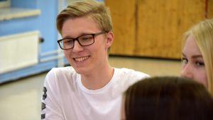 Silmälasipäinen nuori mies istuu pöydän päässä ja nauraa