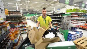 Mies työntää roska-astiaa kaupassa.