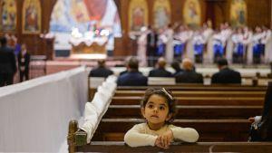 Kopti-kristityt viettävät pääsiäismessua Kairossa. Pieni tyttö istuu selin alttarille.