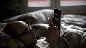 Mies makaa sängyllä ja katsoo matkapuhelinta.