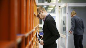 Työntekijä nojaa työpaikkansa postilokerikkoon.