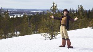 Marko Syysmaan esittämä Nätti-Jussi seisoo Ounasvaaran lumisissa maisemissa.