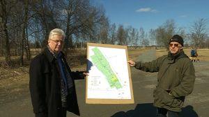 kaksi miestä esittelee alueen karttaa
