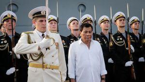 Presidentti Duterte seisoo valkoisessa kauluspaidassa paraatiunivormuissa olevien venäläisten laivastosotilaiden rivin edessä. Hänen vieressään seisoo upseeri valkoisessa univormussa ja koppalakissa pitäen miekka koholla. Taustalla olevilla merisotilailla on valkoiset koppalakit, mustat univormut ja kiväärit, joissa on pistimet kiinnitettyinä.